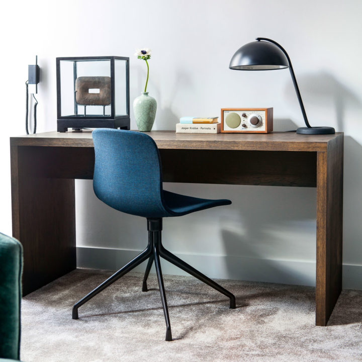 A desk with a radio and some books in a hotel room with blue chair
